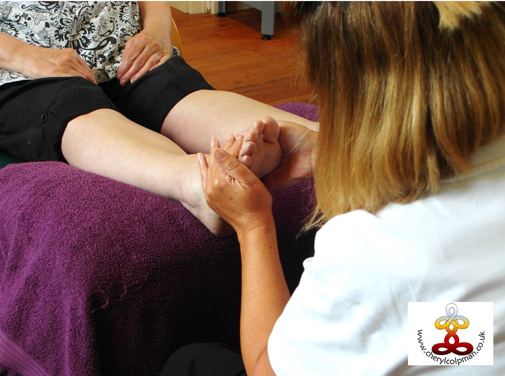 Woman gently holding person's feet giving reiki through the feet training workshop with Cheryl Colpman