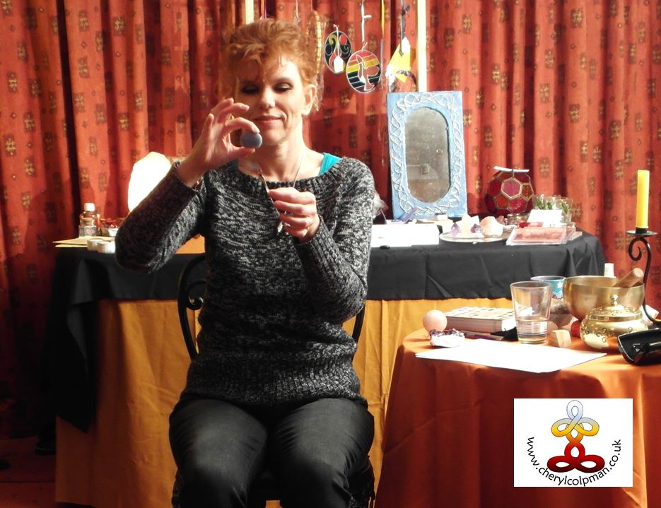 Interesting and relaxed training and workshops person holding crystal with background of crystals stones on work table Cheryl Colpman